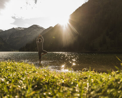 Austria, Tyrol, hiker in yoga pose refreshing in mountain lake - UUF12486