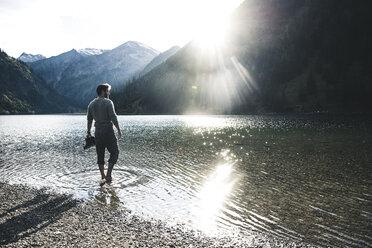 Austria, Tyrol, hiker refreshing in mountain lake - UUF12489