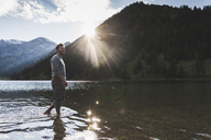 Austria, Tyrol, hiker refreshing in mountain lake - UUF12492