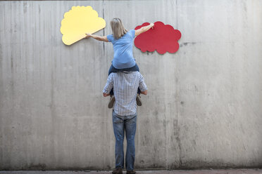 Woman sitting on a man's shoulders attaching colourful cloud shapes to concrete wall - ZEF14868
