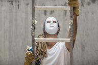 Man wearing a mask climbing a ladder with rope and a can of spray paint - ZEF14871