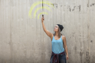 Woman holding up phone looking for signal with wifi sign drawn in yellow chalk on concrete wall - ZEF14874