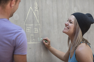 Man and woman drawing a house with chalk on concrete wall - ZEF14877