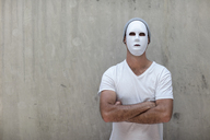 Man wearing a mask standing next to a concrete wall - ZEF14880