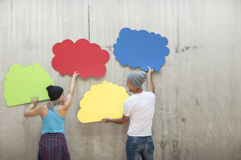 Man and woman attaching colourful cloud shapes to concrete wall - ZEF14883