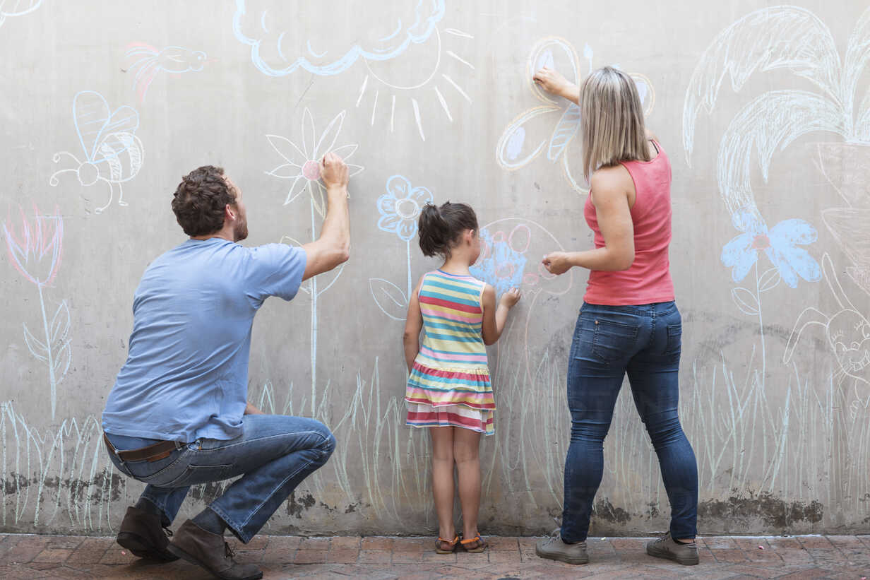 Family drawing colourful pictures with chalk on a concrete wall - ZEF14886 - zerocreatives/Westend61