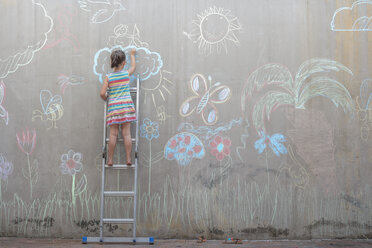 Girl standing on ladder drawing colourful pictures with chalk on a concrete wall - ZEF14889