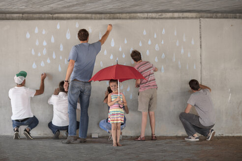 People drawing raindrops on concrete wall, little girl standing holding red umbrella - ZEF14892