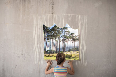 Girl holding a picture of a forest on concrete wall with a chalk drawn border - ZEF14895