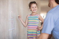 Father and daughter playing tic tac toe with chalk on a concrete wall - ZEF14898