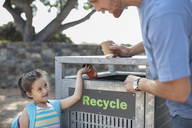 Girl with father putting a drink can in a recycle bin - ZEF14901