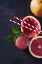 Whole and sliced Pink Grapefruit, leaves, straws and glass of grapefruit juice - CSF28594