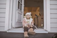 Young girl sitting in entrance, cardboard box - KMKF00093