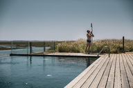 Man taking a shower on the edge of a modern infinity swimming pool - MFF04228