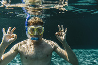 Portrait of man with diving goggles and snorkel underwater in a swimming pool making ok sign - MFF04237