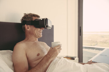Man wearing VR glasses in bed holding cup of coffee - MFF04249