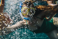 Portrait of woman with diving goggles and snorkel underwater in a swimming pool - MFF04252