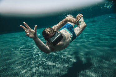 Man diving in a swimming pool wearing VR glasses - MFF04258