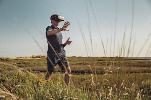 Mature man wearing VR glasses walking trough grass - MFF04261