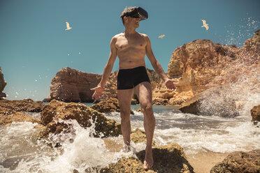 Mature man wearing VR glasses between rocks on beach - MFF04264