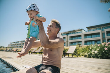 Happy father and baby son at the poolside during summer vacation - MFF04267