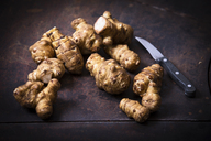Jerusalem artichokes and kitchen knife on rusty ground - MAEF12466