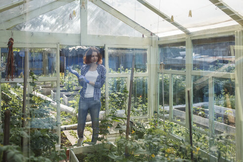 Smiling young woman standing in a greenhouse - VPIF00269
