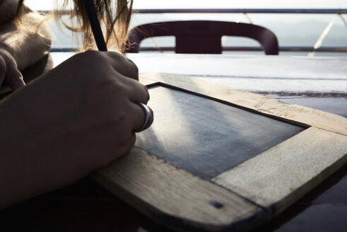 Woman writing on chalkboard, close-up - IGGF00253