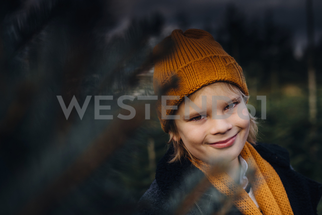 Portrait of a boy standing by Christmas tree, smiling - MJF02204