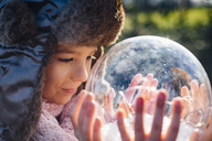 Brother and sister looking into crystal ball filled with snow, making a wish - MJF02213