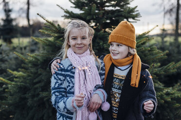 Boy and girl holding sparkler in front of fir trees - MJF02225
