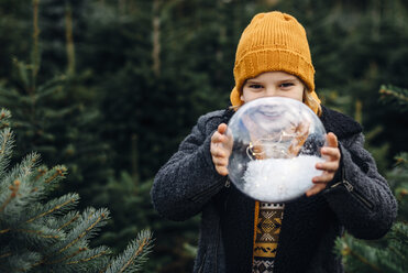 Little boy holding a snow-filled crystal ball, making a wish - MJF02228