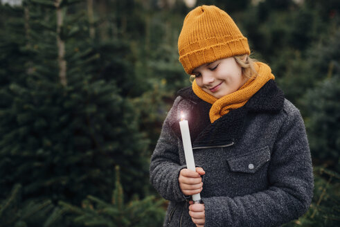 Little boy standing in front of fir trees with a burning candle - MJF02231