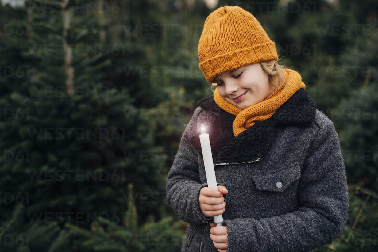 Little boy standing in front of fir trees with a burning candle - MJF02231 - Jana Mänz/Westend61