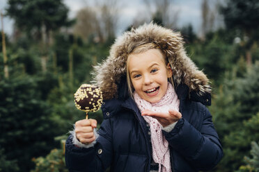 Little girl standing in front of fir trees holding chocolate dipped apple - MJF02243
