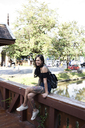 Portrait of a happy tattooed woman sitting on a wooden bridge - IGGF00254