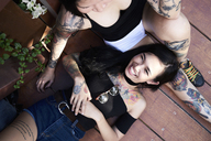 Happy woman lying on leg of tattooed girl friend on planks - IGGF00257