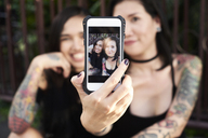 Woman holding cell phone with selfie of herself with her lesbian partner - IGGF00263