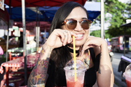 Portrait of happy woman drinking a smoothie outdoors - IGGF00266