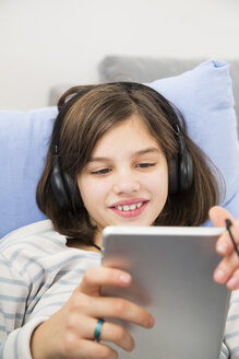 Portrait of smiling girl using tablet and headphones at home - LVF06509