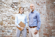 Portrait of two business colleagues at stone wall - VABF01414