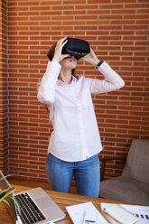 Businesswoman wearing VR glasses in office - VABF01447
