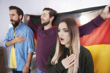 Football fans with German flag singing national anthem - ABIF00075
