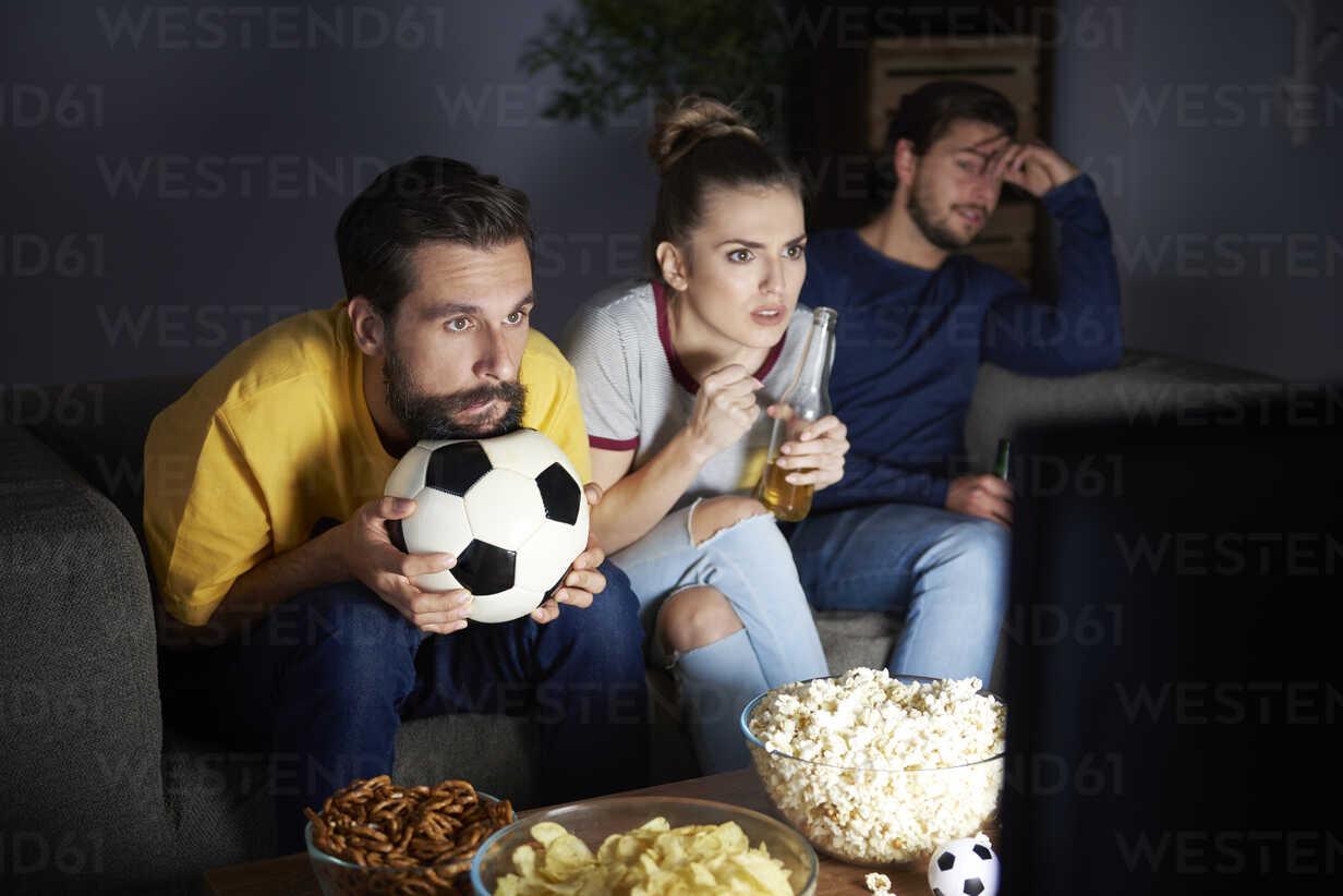 Worried friends sitting on the sofa watching Tv - ABIF00093 - gpointstudio/Westend61
