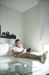 Smiling young man relaxing at home with his smartphone - RAEF01948
