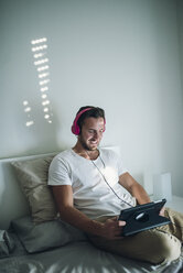 Smiling young man relaxing at home with his tablet - RAEF01951