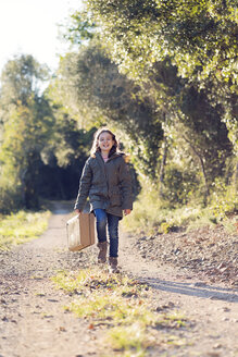 Happy girl walking with suitcase in nature - XCF00164