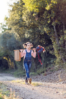 Girl walking with suitcase and hobby horse in nature - XCF00167
