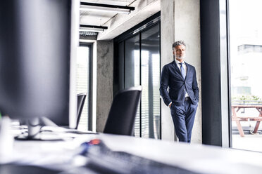 Mature businessman standing in office thinking - HAPF02512