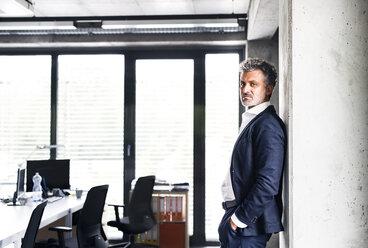 Portrait of confident mature businessman standing in office - HAPF02515